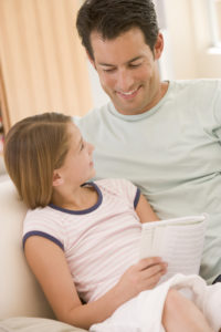 Father and daughter in living room reading book and smiling